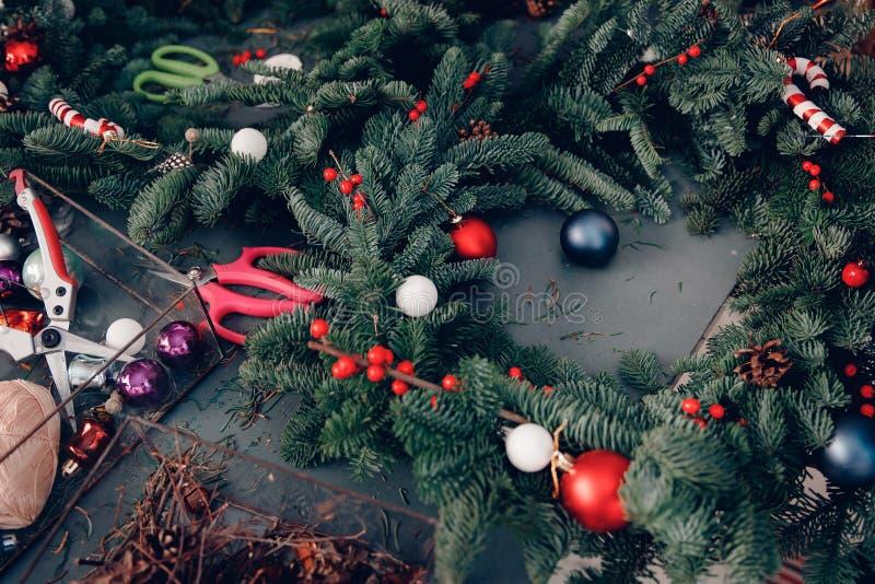 La guirnalda del árbol de navidad que adornaba el taller DIY fijó las tijeras para hacer en la tabla foto de archivo
