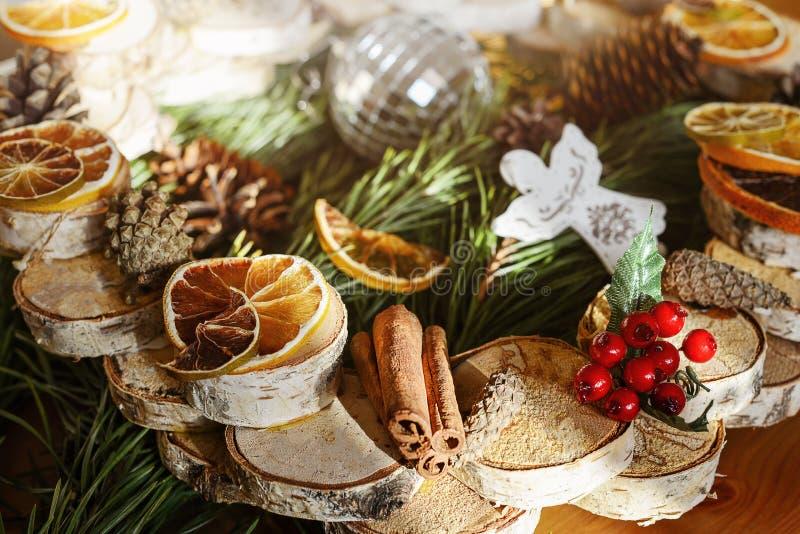 La guirnalda hecha en casa de la fruta cítrica corta la madera y ramas secas spruce foto de archivo