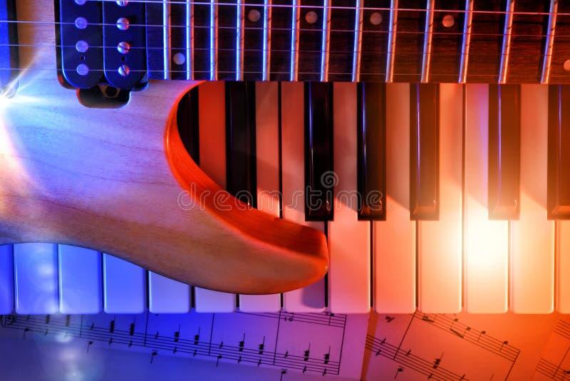 La guitare électrique et le synthétiseur avec les lumières rouges et bleues complètent images stock
