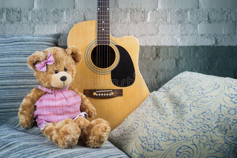 La guitare acoustique sur un sofa avec des oreillers et un nounours concernent le fond d'un mur de briques blanc image libre de droits