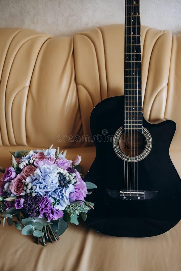 La guitare et le bouquet sont sur un sofa en cuir images libres de droits