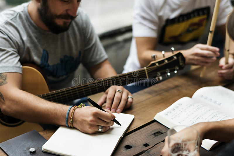 La guitarra del juego de los hombres escribe ensayo de la música de la canción foto de archivo libre de regalías