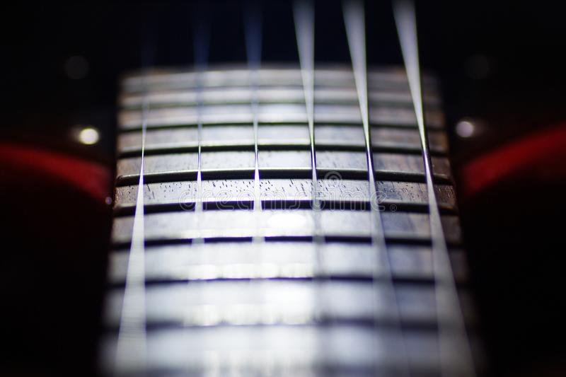 La guitarra eléctrica roja en macro, secuencias se cierra para arriba, detalle del instrumento del músico fotos de archivo libres de regalías
