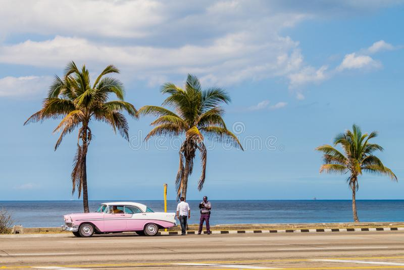 LA HABANA, CUBA - 22 DE FEBRERO DE 2016: Coche rosado viejo en una impulsión de la playa en La Habana imagen de archivo
