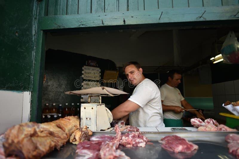 La Habana, Cuba, el 14 de agosto de 2018: Carnicero que vende la carne fresca en La Habana foto de archivo