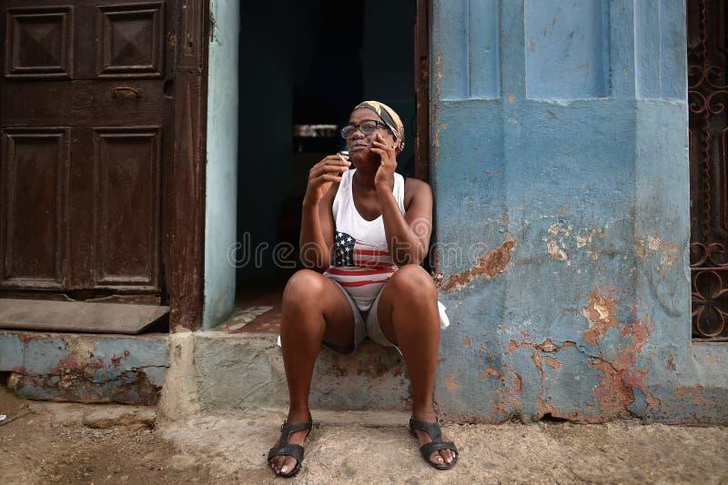 La Habana, Cuba, el 14 de agosto de 2018: Mujer que se sienta y que fuma en las calles de La Habana foto de archivo