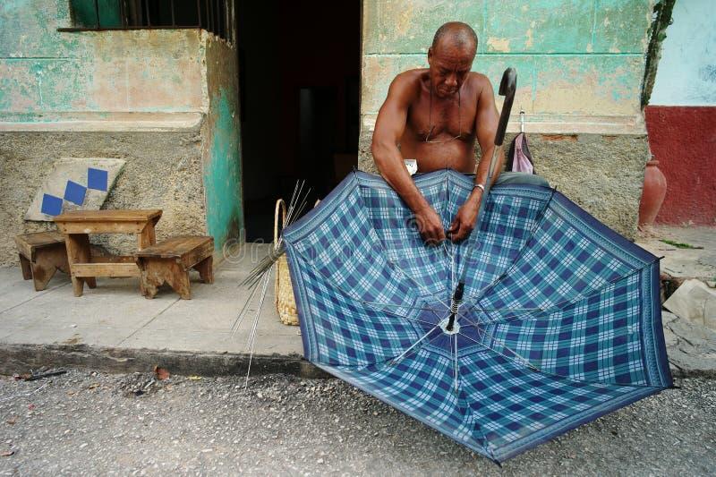 La Habana, Cuba, el 5 de junio de 2016: Un hombre que tiene el negocio de reparar el paraguas fotografía de archivo libre de regalías