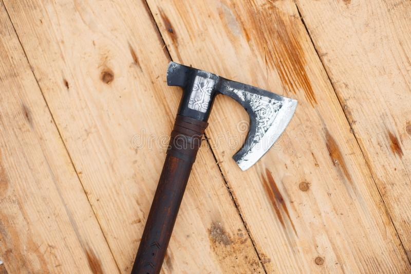 La hache de bataille des Vikings se trouve sur un bouclier en bois photos stock