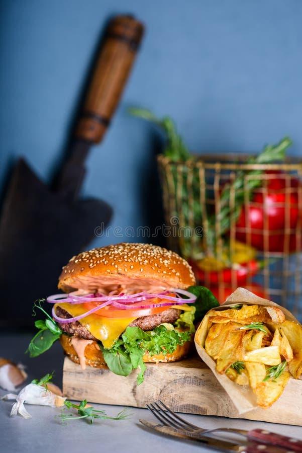 La hamburguesa asada a la parrilla de la carne de vaca con lechuga y mayonesa sirvi? las patatas fritas foto de archivo