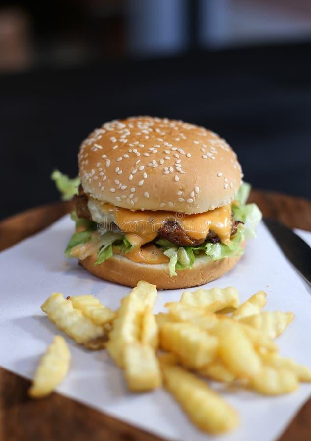 La hamburguesa con las patatas fritas sirvió en una placa de madera imagen de archivo