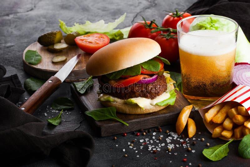 La hamburguesa fresca de la carne de vaca con la salsa y las verduras y vidrio de cerveza de cerveza dorada del arte con las pata fotografía de archivo