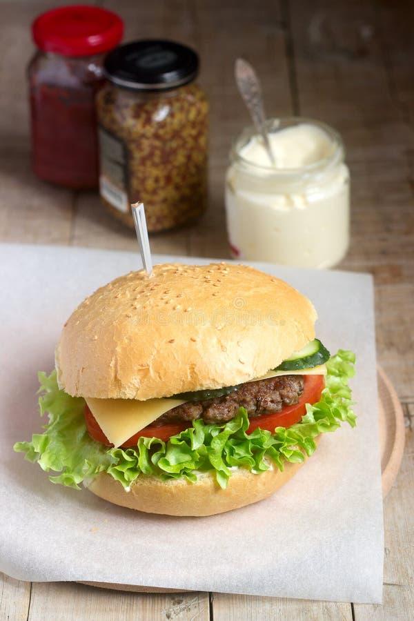 La hamburguesa hecha en casa con las verduras frescas sirvió con las diversas salsas imágenes de archivo libres de regalías