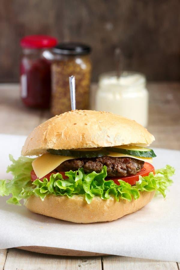 La hamburguesa hecha en casa con las verduras frescas sirvió con las diversas salsas fotos de archivo libres de regalías