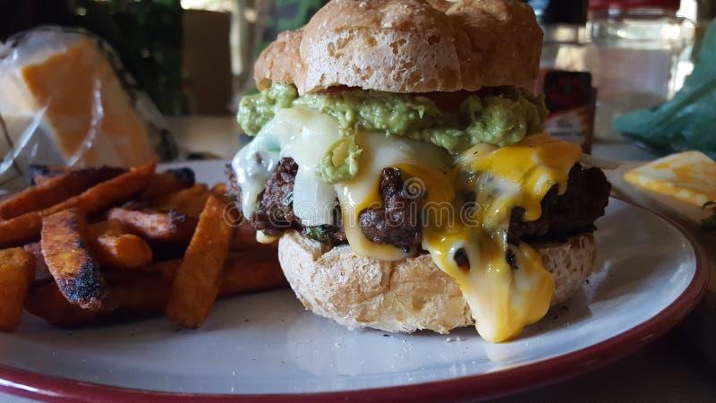 La hamburguesa hecha en casa del quacamole en el gluten libera el bollo foto de archivo