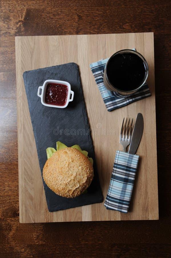 La hamburguesa, la cerveza y la baya sauce en el barco de salsa blanco en una base, un vidrio y cubiertos de la pizarra servidos  fotos de archivo libres de regalías
