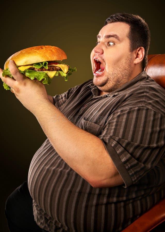 La hamburguesa que come al hombre de la competencia de los alimentos de preparación rápida come con el hamberger del apetito foto de archivo