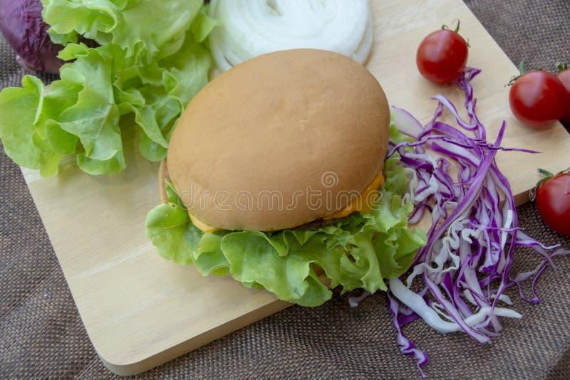 La hamburguesa se prepara con cerdo asado a la parrilla, queso, los tomates, la lechuga y la col púrpura en la tabla imagenes de archivo