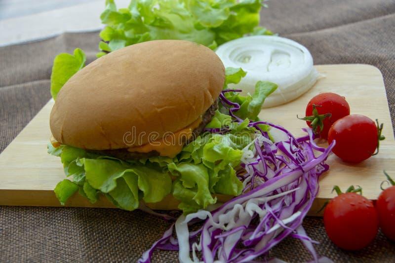 La hamburguesa se prepara con cerdo asado a la parrilla, queso, los tomates, la lechuga y la col p?rpura en la tabla fotografía de archivo libre de regalías