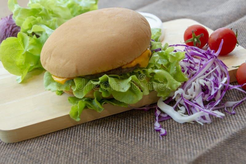 La hamburguesa se prepara con cerdo, queso, los tomates, la lechuga y las cebollas asados a la parrilla en un piso de madera rect imagenes de archivo