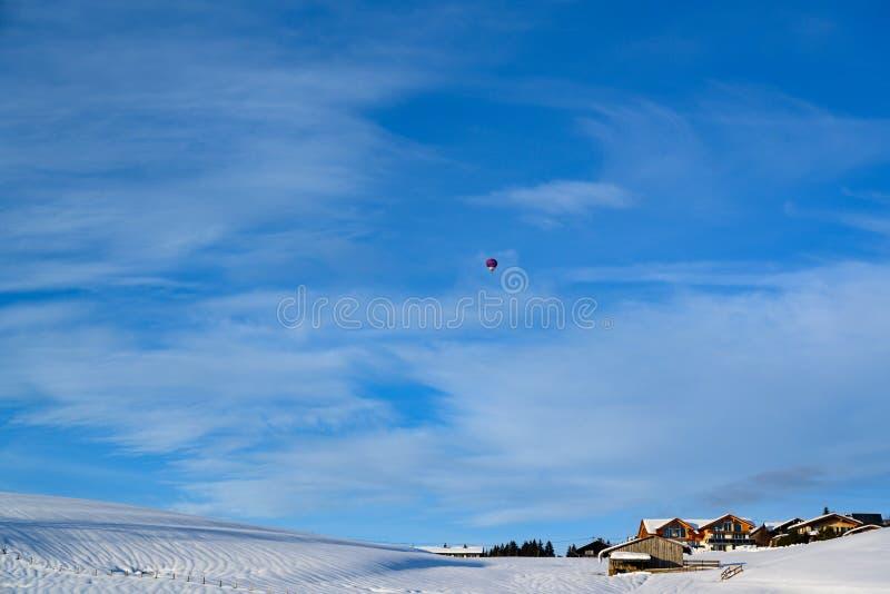 La haute de montgolfière au-dessus des maisons de ferme dans la neige a couvert le paysage de la Bavière, Allemagne photographie stock libre de droits