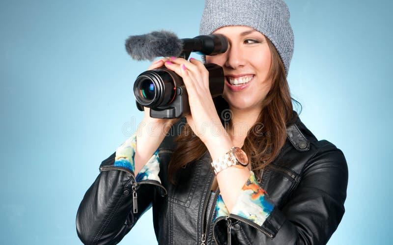 La hembra adulta joven de la cadera señala la cámara de vídeo foto de archivo