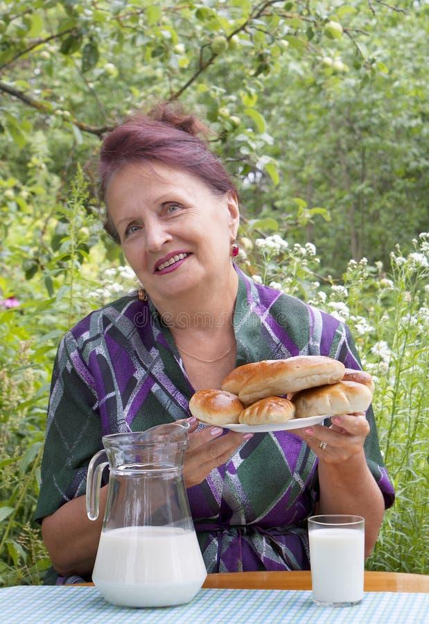 La hembra adulta y las empanadas cocidas al horno apetitosas de la casa fotografía de archivo