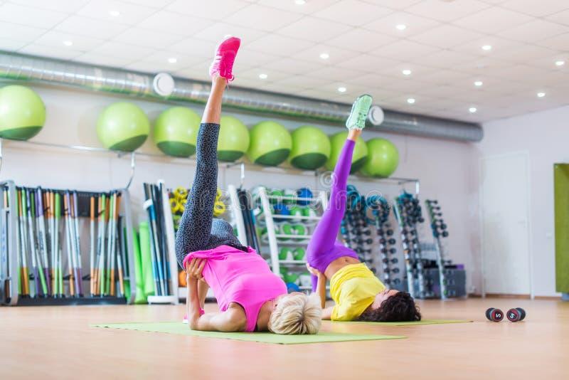 La hembra atl?tica apta que hace solo ejercicio del puente de la pierna en las esteras en el grupo clasifica en gimnasio contra e imagenes de archivo