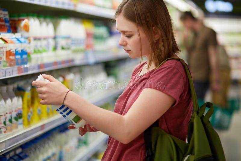 La hembra atractiva va a hacer compras, se coloca en el departamento de la lechería, botella de los controles de leche, lee la in imagenes de archivo