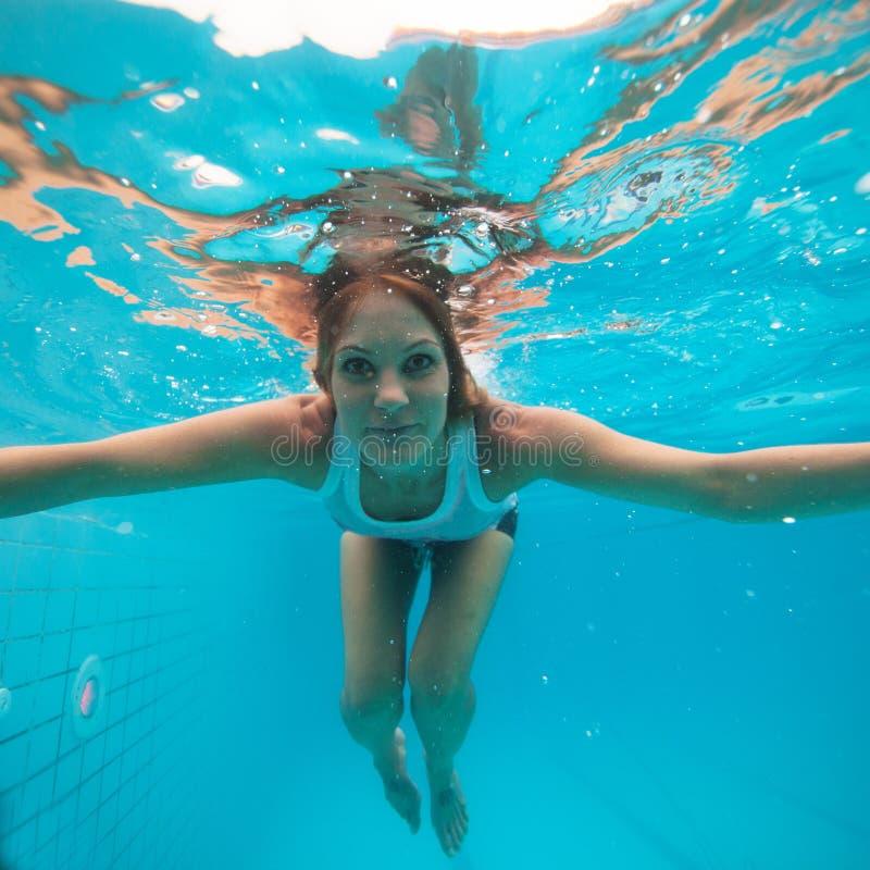 La hembra con los ojos se abre bajo el agua en piscina imagen de archivo libre de regalías