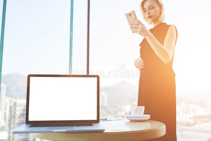 La hembra confiada joven está buscando la información vía el teléfono móvil fotografía de archivo