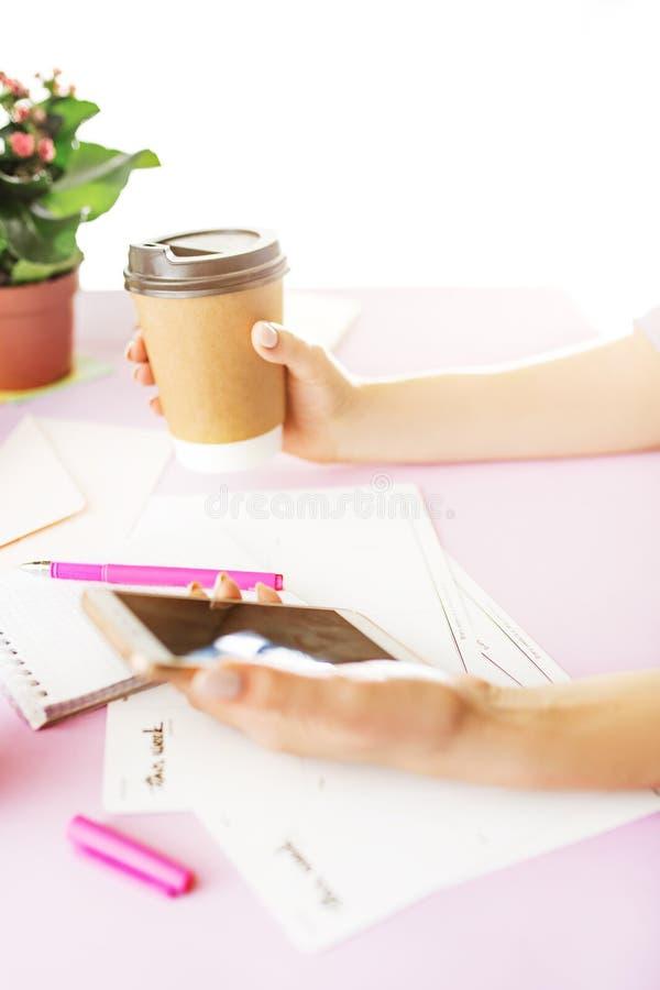 La hembra da sostener el teléfono y el café en el escritorio rosado de moda imagen de archivo libre de regalías