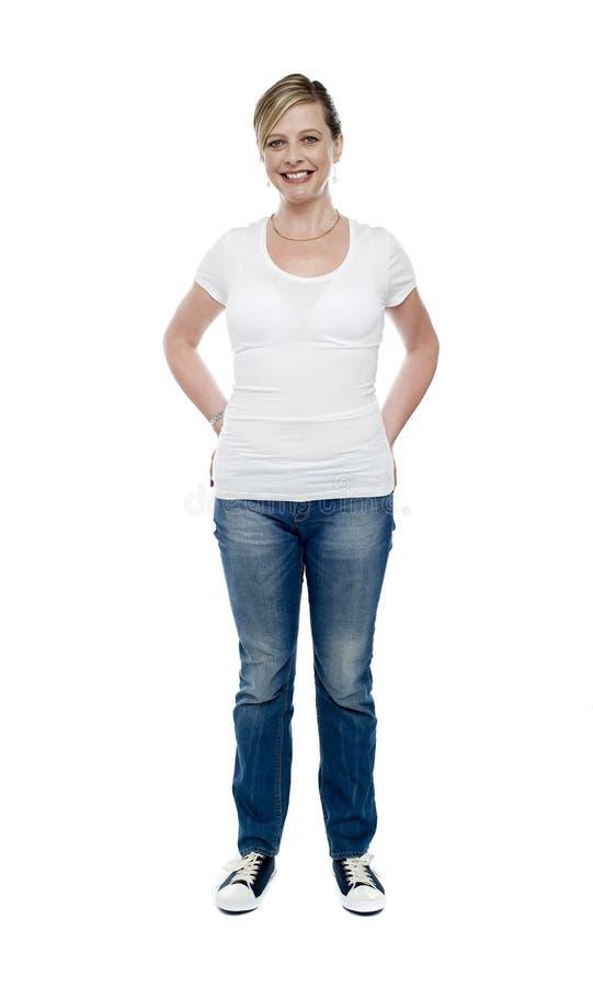 La hembra de moda ocasional con las manos en pantalones vaqueros embolsa fotos de archivo