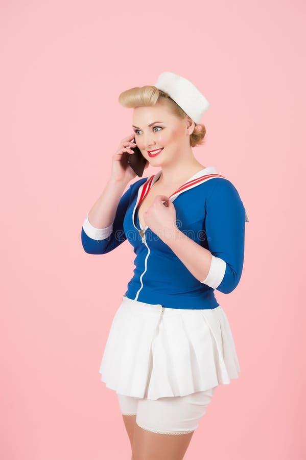 La hembra del estilo del animado habla sobre el Smart-teléfono en fondo color de rosa Muchacha atractiva del marinero con maquill foto de archivo