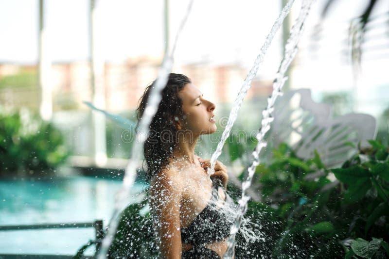 La hembra delgada atractiva en traje de ba?o toma la ducha en piscina entre los arbustos verdes en tejado con el fondo del scape  fotos de archivo libres de regalías
