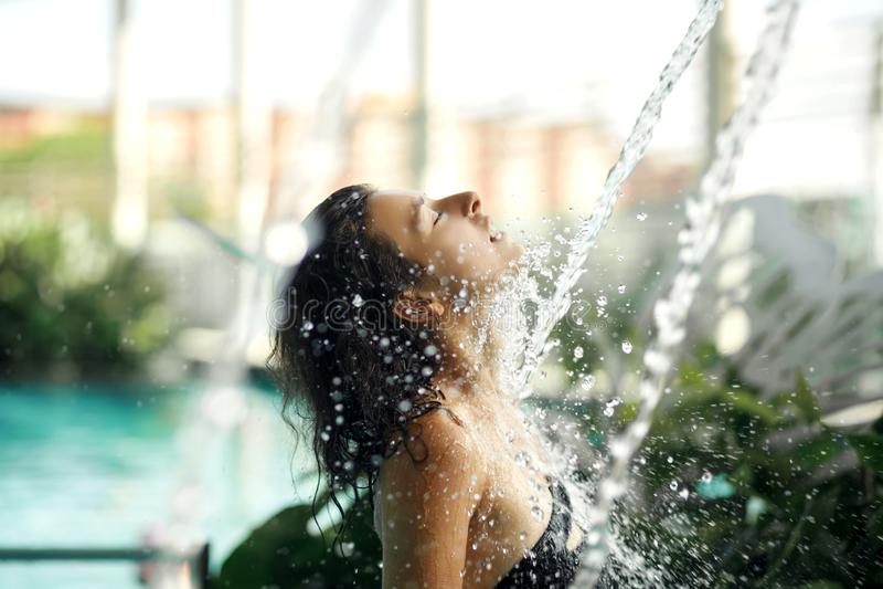 La hembra delgada atractiva en traje de ba?o toma la ducha en piscina entre los arbustos verdes en tejado con el fondo del scape  imagen de archivo libre de regalías