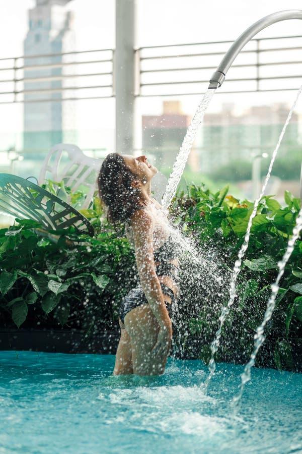 La hembra delgada atractiva en traje de ba?o toma la ducha en piscina entre los arbustos verdes en tejado con el fondo del scape  fotos de archivo