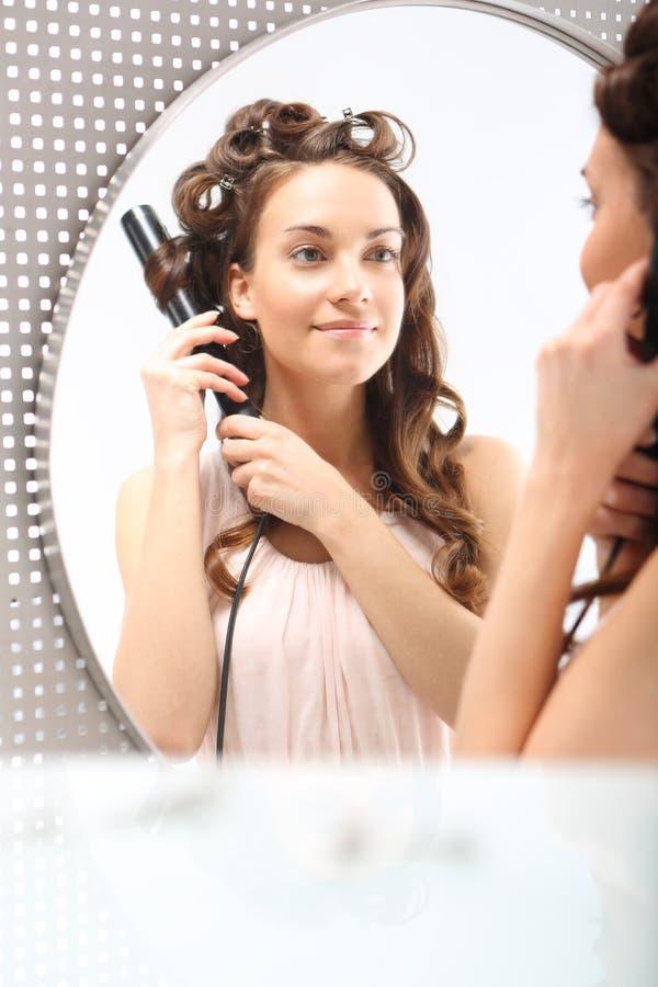La hembra enrolla el pelo en el hierro que se encrespa fotografía de archivo libre de regalías
