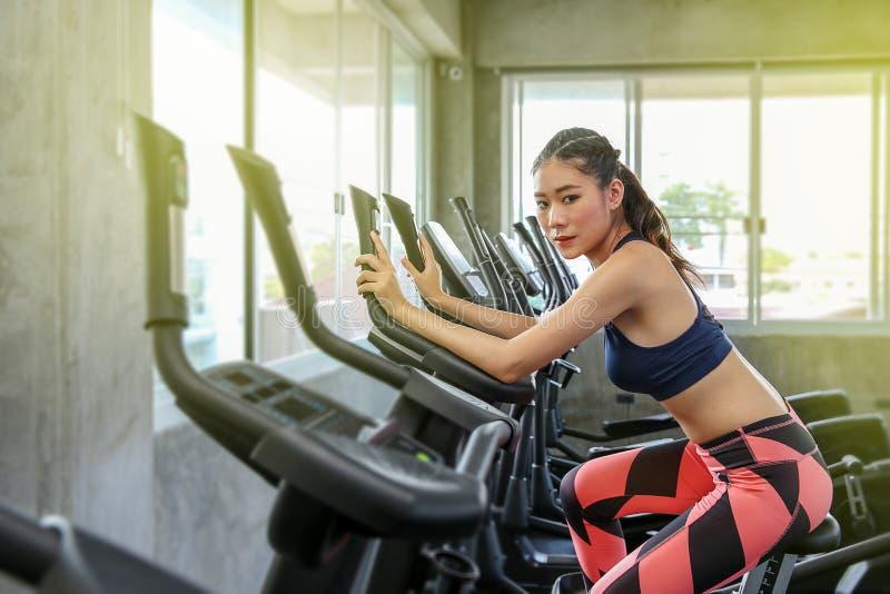 La hembra está completando un ciclo en el gimnasio Retrato de las mujeres que ejercitan en las máquinas cardiias en el club de de imagenes de archivo