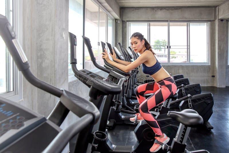 La hembra está completando un ciclo en el gimnasio Retrato de las mujeres que ejercitan o foto de archivo
