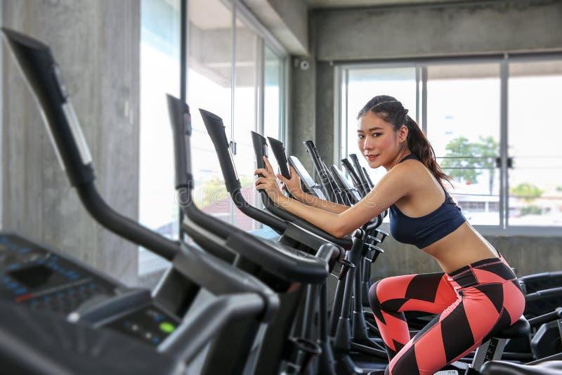 La hembra está completando un ciclo en el gimnasio Retrato de la muchacha que ejercita en las máquinas cardiias en el club de dep fotos de archivo