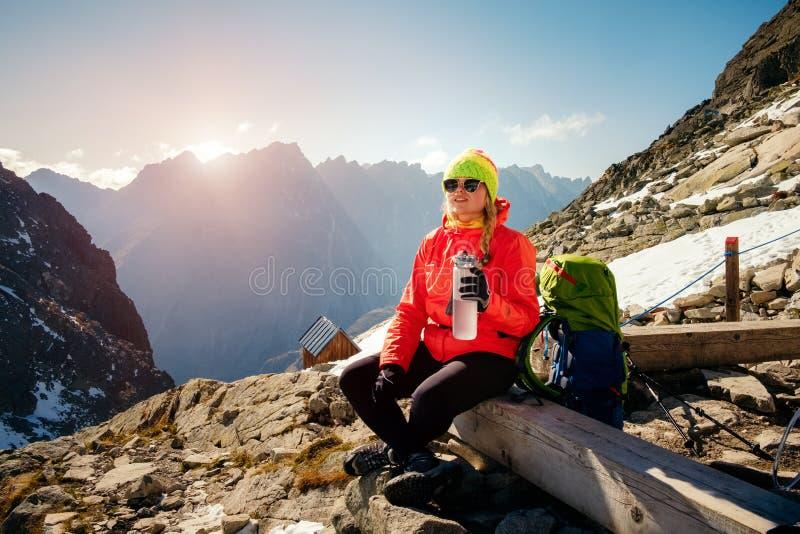 La hembra goza de paisaje de la montaña y del agua potable después de subir foto de archivo libre de regalías