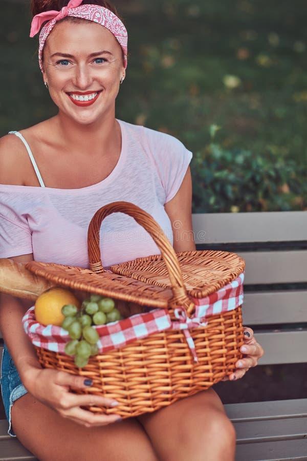 La hembra hermosa feliz del pelirrojo que lleva la ropa casual sostiene una cesta de la comida campestre mientras que se sienta e foto de archivo libre de regalías