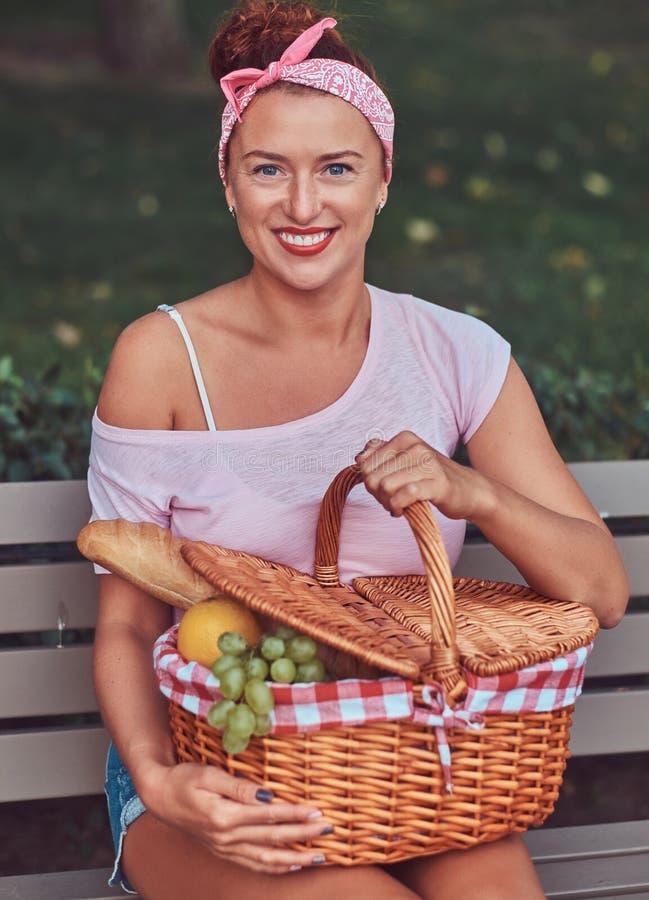 La hembra hermosa feliz del pelirrojo que lleva la ropa casual sostiene una cesta de la comida campestre mientras que se sienta e foto de archivo