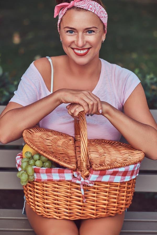 La hembra hermosa feliz del pelirrojo que lleva la ropa casual sostiene una cesta de la comida campestre mientras que se sienta e imágenes de archivo libres de regalías