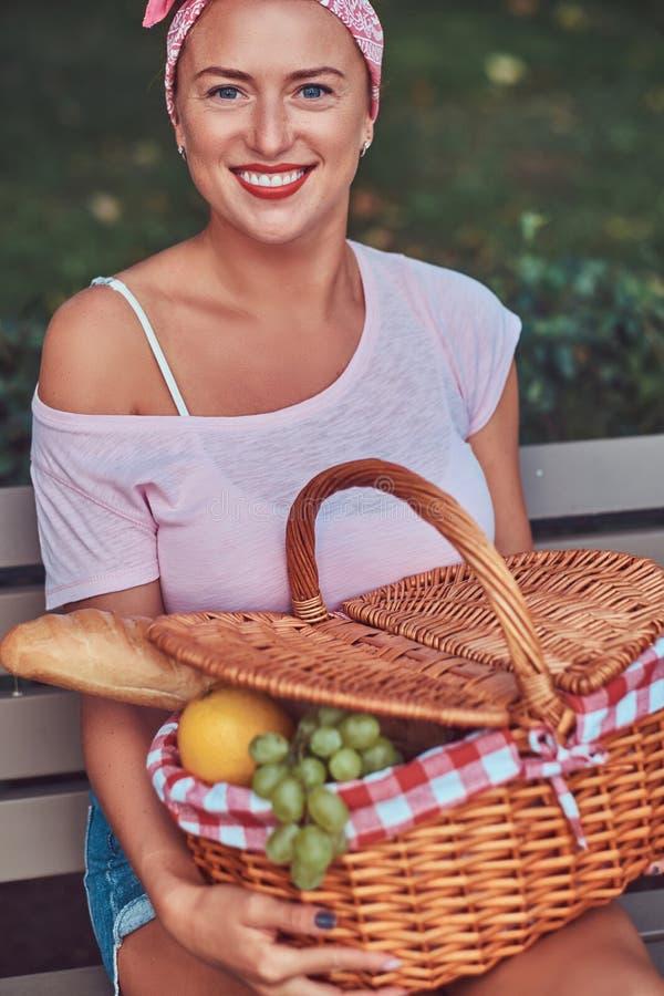 La hembra hermosa feliz del pelirrojo que lleva la ropa casual sostiene una cesta de la comida campestre mientras que se sienta e fotos de archivo libres de regalías