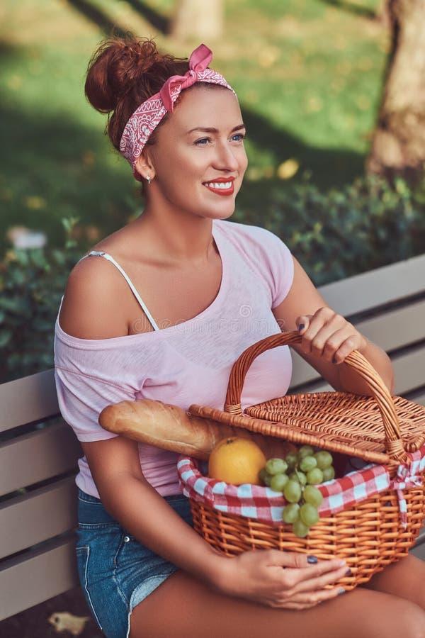 La hembra hermosa feliz del pelirrojo que lleva la ropa casual sostiene una cesta de la comida campestre mientras que se sienta e fotografía de archivo libre de regalías