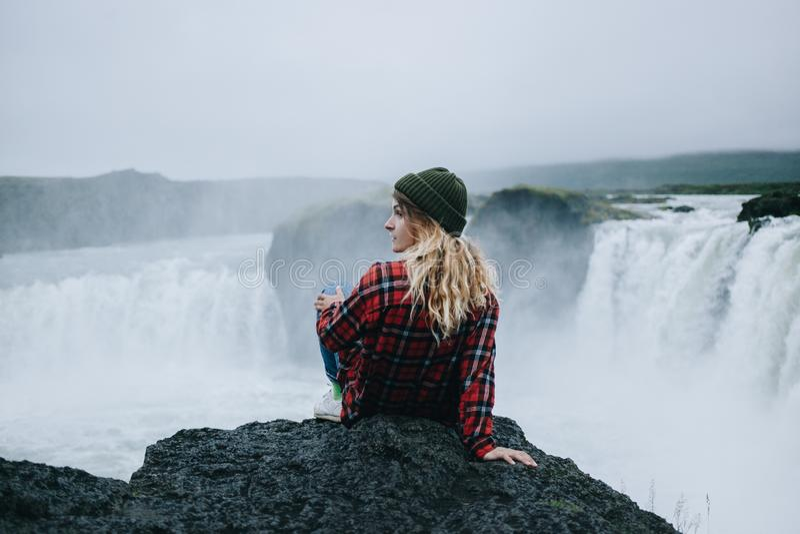 La hembra joven bonita se sienta en el borde del acantilado Islandia imagen de archivo libre de regalías