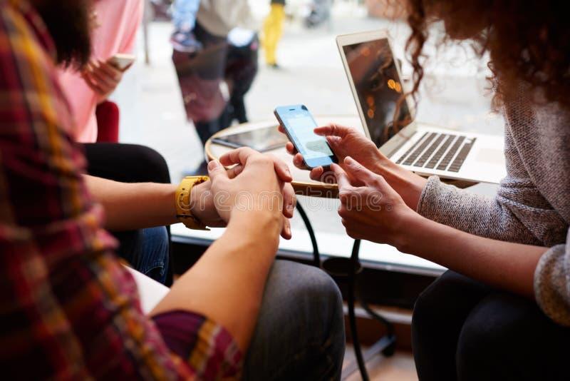 La hembra joven está leyendo la información en la página web vía su teléfono móvil fotos de archivo