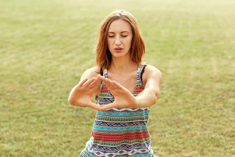 La hembra joven hermosa se relaja en actitud de la yoga en naturaleza verde Mujer de la belleza que hace yoga Concepto sano y de  fotos de archivo libres de regalías