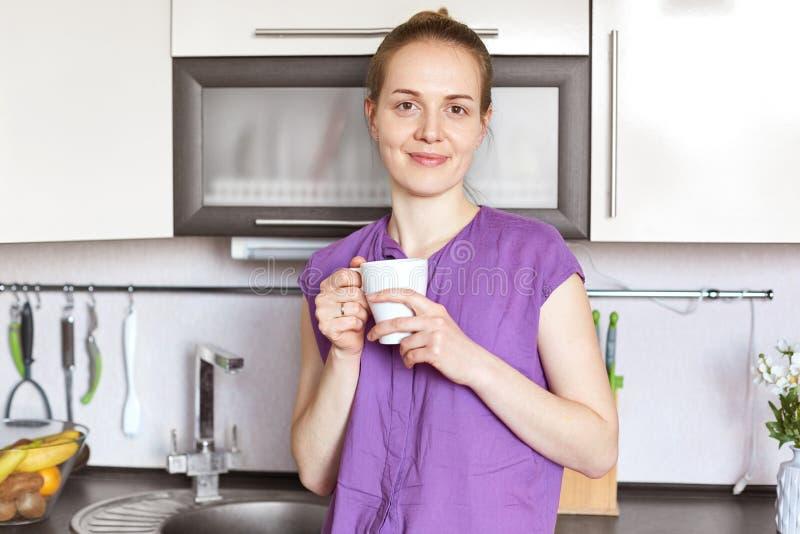 La hembra joven positiva sin compone, lleva la ropa casual, la taza blanca de los controles con la bebida, las bebidas té o el ca imagenes de archivo
